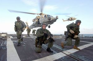 US Navy Seals fast rope on to a ship's deck.  U. S. Navy photo by Photographer's Mate 1st Class (AW) Michael W. Pendergrass